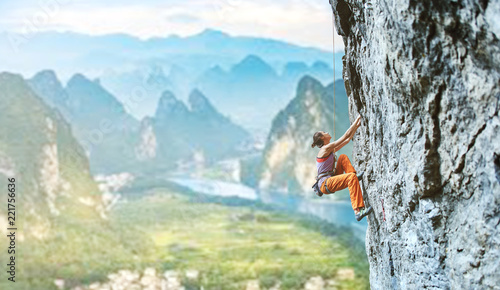 Fotografie, Obraz  young slim female rock climber climbing on the cliff