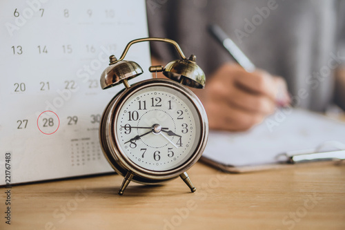 Fototapeta due date calendar with alarm clock on office desk and blur business woman working in background  obraz