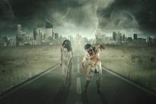 Two Creepy Zombies Walking On The Asphalt Road