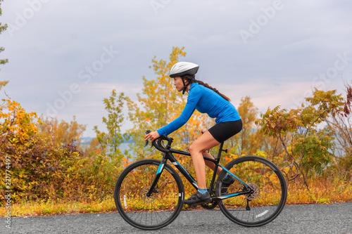 Biking road bike girl in autumn. Active sport fitness exercise in fall season.