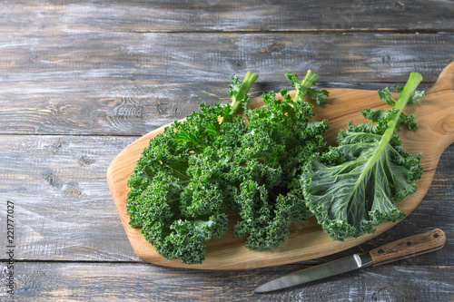 Fresh green curly kale leaves on a cutting board on a wooden table. free space. selective focus. rustic style. healthy vegetarian food