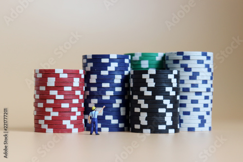 Foto  Miniature man pointing to a pile of casinos chips.