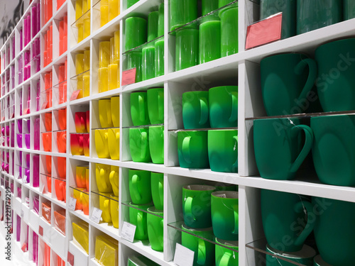 cups of different colors stand In shop window