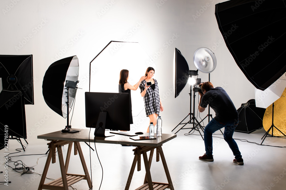 Fototapety, obrazy: Photographer and pretty model working in modern lighting studio with many kinds of flash and accessories.
