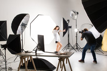 Photographer And Pretty Model Working In Modern Lighting Studio With Many Kinds Of Flash And Accessories.