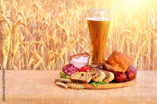 Tuinposter Bier / Cider beer in a glass, sausage, vegetables on a table