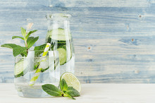 Healthy Spring Beverage In Bottle And Glass With Green Cucumber, Mint, Lime, Straw  On Soft Blue Wooden Background. Copy Space.