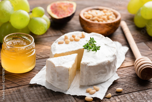 Brie or camembert cheese on brown wooden table served with green grapes, pine nuts, honey and figs. Closeup view. Tasty white cheese