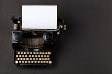 Vintage Typewriter Top Down Flatlay Shot From Above With Empty, Blank Sheet Of Paper On Black
