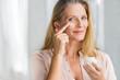 Leinwandbild Motiv Woman applying anti aging lotion on face
