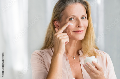 Woman applying anti aging lotion on face Wallpaper Mural