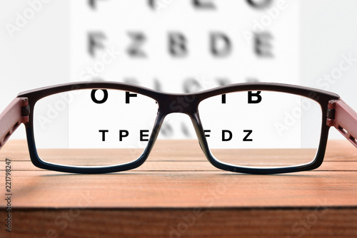 Fotografie, Obraz Glasses on table and alphabet letter front view