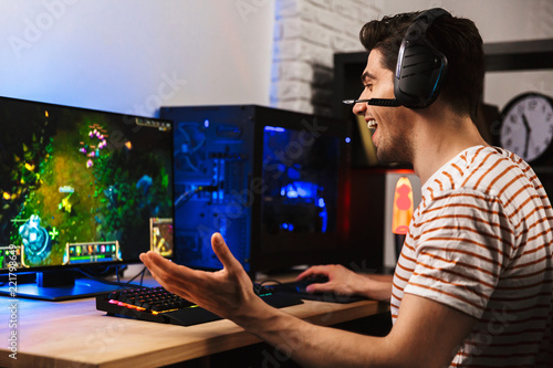 Valokuva Image of cheerful gamer man playing video games on computer, wearing headphones