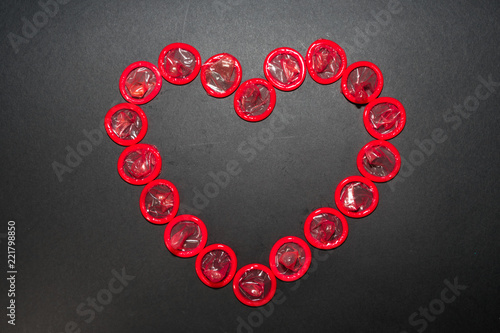 Foto The heart is laid out with red condoms on a black background