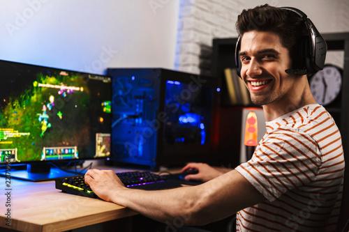 Fotomural Image of cheerful gamer man playing video games on computer, wearing headphones