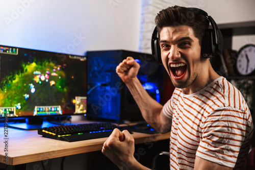 Carta da parati Portrait of happy man playing video games on computer, wearing headphones and us