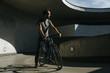Vorderansicht von männlichem Radfahrer, der in einer urbanen Landschaft auf seinem Fahrrad fährt