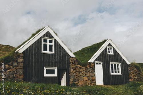 Obraz Black farmhouse in Skaftafell National Park under cloudy sky in Iceland - fototapety do salonu