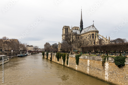 Fotografiet  Side view of the Notre-Dame Cathedral in Paris with a moody sky