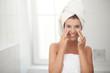 canvas print picture - Junge hübsche Frau trägt Gesichtscreme auf