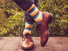 Office Manager In Stylish Shoes, Blue Jeans And Bright, Colorful Socks Against The Background Of Green Trees. Lifestyle, Fashion, Fun
