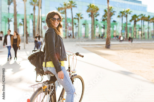 Fotografie, Obraz  Back view poositive brunette girl in sunglasses  going by bike in sunny morning on street with palms