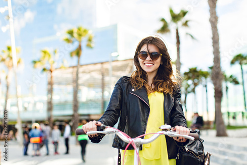 Obraz na plátně  Portrait of positive brunette girl with bike on street with palms