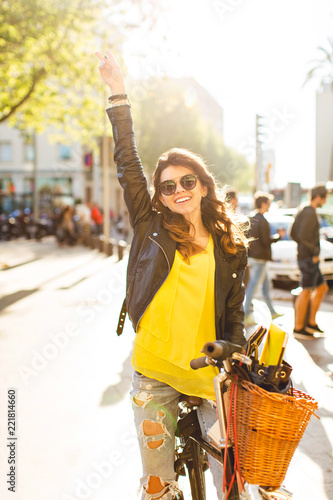 Fotografie, Obraz  Happy brunette gir in sunglasses is posing on bike on sunny street in city