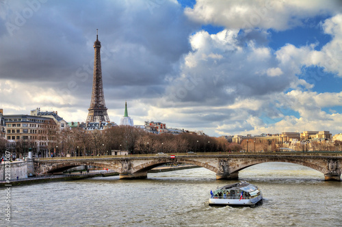 Printed kitchen splashbacks Tourist boat at the Seine in Paris with the Eiffel tower in the background on a cloudy winter day