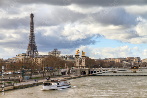 Tourist boat at the Seine in Paris with the Eiffel tower in the background on a Fotobehang