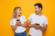 canvas print picture - Happy excited young loving couple standing isolated over yellow wall background using mobile phones.