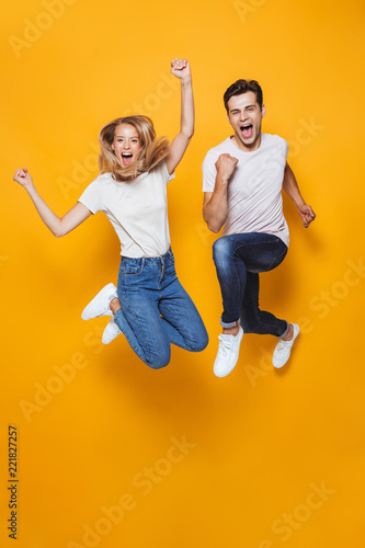 Papel de parede Young loving couple jumping isolated over yellow wall background.