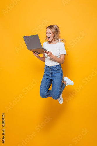 Photo Excited young woman jumping isolated over yellow wall background using laptop computer