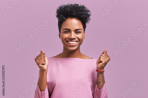 Fotografie, Obraz  Portrait of overjoyed female clenches fists with with happiness, opens mouth widely as shouts loudly, celebrates her success, poses against lavender background