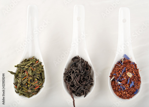 Fotografering  Assortment of dry tea rooibos, black, green, in white ceramic spoon