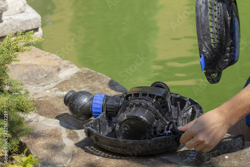 Fotografie, Obraz  Repair of the water pump for a small decorative pond with a fountain