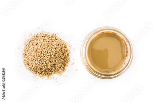 Tahini and sesame seeds isolated on white background. Top view