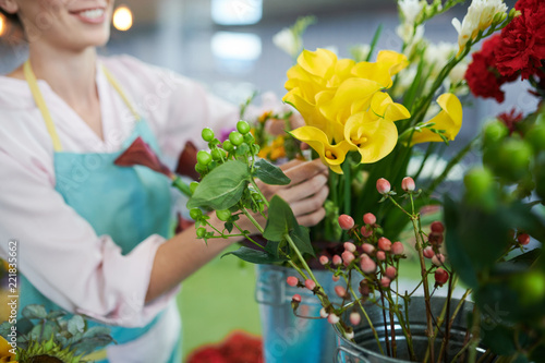 Foto op Canvas Bloemen Closeup of unrecognizable female florist arranging beautiful yellow flowees at counter in small flower shop, copy space