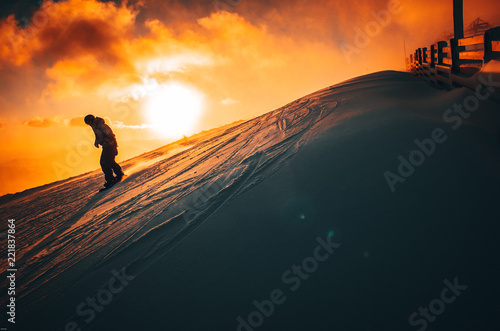 Snowboarder in winter ski resort. Sunset in background