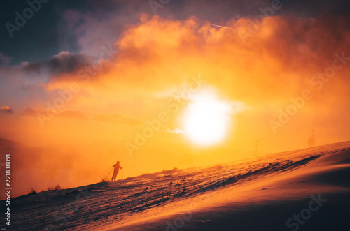 landscape magical sunrise sky with winter silhouette of skier in background.