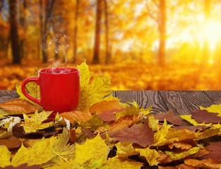 Fototapeta Autumn leaves and hot steaming cup of coffee.