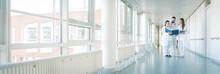 Drei Ärzte Im Flur Von Krankenhaus Unterhalten Sich Kurz