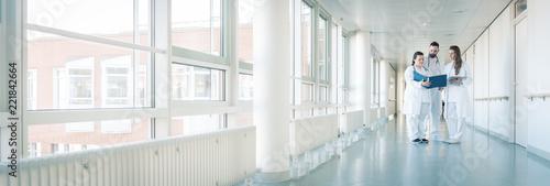 Fotografia  Drei Ärzte im Flur von Krankenhaus unterhalten sich kurz