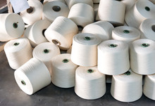 Many Rolls Of Industrial White Cotton Fabric For Clothing Cloth Textile Manufacture On Machine. Many Reels Of Thread Spools In Spinning Factory.