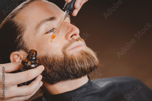 Fotografija Oil for beard in dropper, process of moisturizing hair.