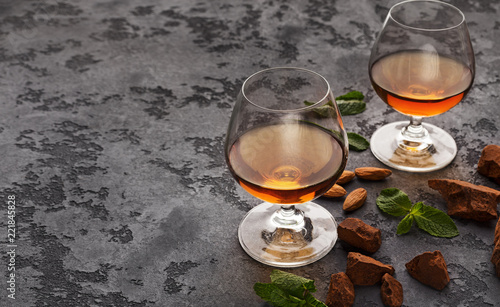 Two glasses with cognac, whiskey stones and almonds