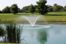 The Flowing Water Fountain In The Park On A Sunny Day.