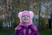 Little Girl In A Hat Looks Up Against A Background Of Autumn Trees. Autumn Has Come.