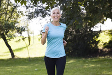 Senior Woman Jogging Through Park