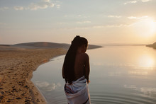 Young Woman Watching The River And Sunset